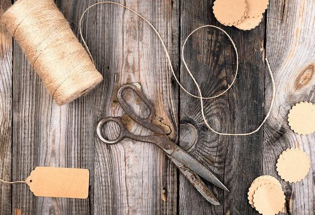 Spule des braunen seils, der papiertags und der alten scheren auf einem grauen holz