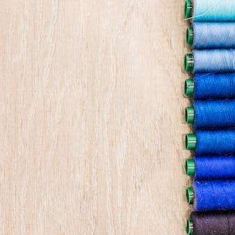 Spule von threads in der reihe auf hölzernem hintergrund