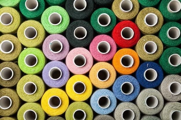 Spulen mit buntem faden, hintergrund in verschiedenen farben