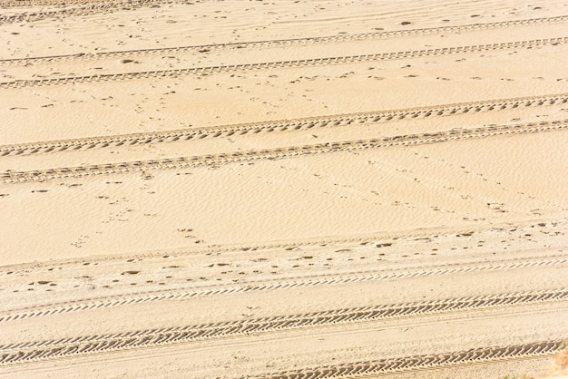 Spuren von autoreifen im sand als hintergrund