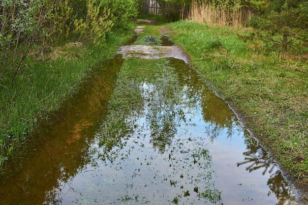 Spurrillen einer unbefestigten straße in der überschwemmungsebene eines flusses unter wasser während eines hochwassers