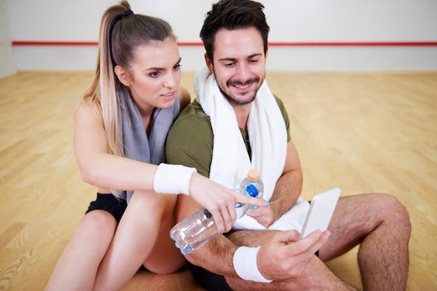 Squash-freunde mit handy-ausruhen