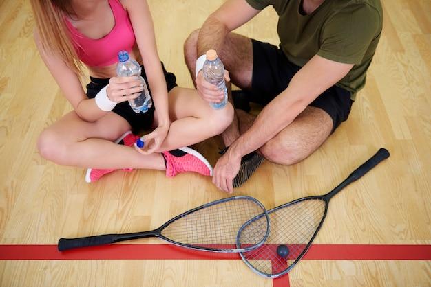 Squashspieler mit einer flasche wasser ruhen