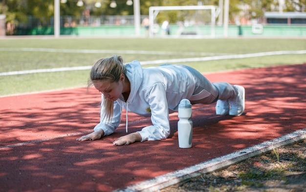Squatting.young schönheitsmädchen machen übungen im stadion