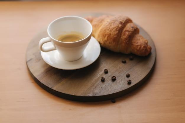 Sroissant und tasse kaffee auf holztisch. morgen zu hause.