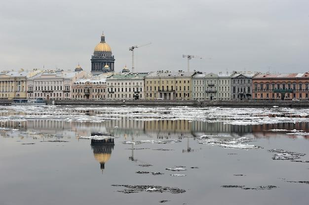 St. isaac's cathedral und der baukran spiegeln sich in der newa im frühjahr, st. petersburg, russland