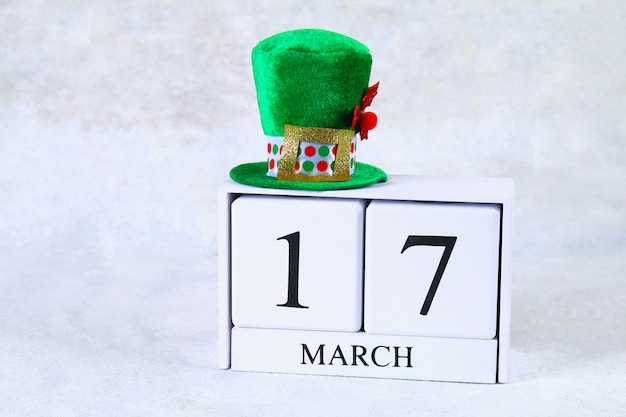 St.patrick's day. ein hölzerner kalender, der 17. märz zeigt. grüner hut und bogen.