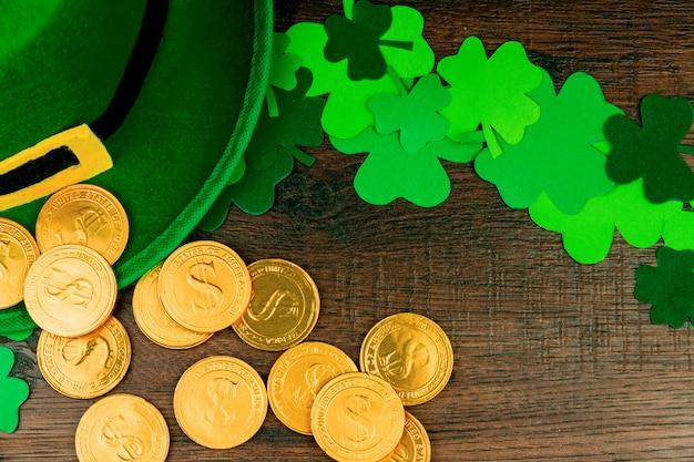 St. patrick's day. goldmünzen, klee mit drei blumenblättern des grüns, grüner hut des kobolds auf holztisch