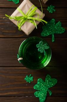 St. patrick's day green beer pint über dunkelgrünem tisch, dekoriert mit kleeblattblättern. patrick day pub party, feiern.