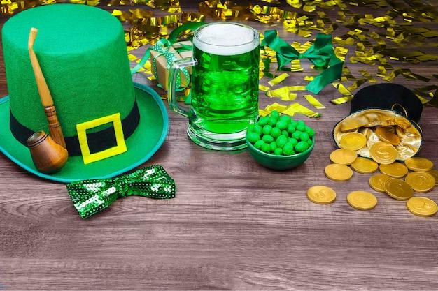 St. patrick's day. grüner hut des kobolds mit grünem halben liter bier, goldmünzen, pfeife und grünen süßigkeiten auf holztisch
