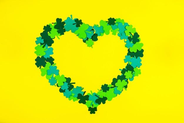 St. patrick's day. herzform des klees mit drei blumenblättern des grüns, der auf gelbem hintergrund liegt