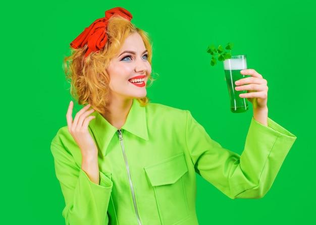 St. patrick's day. lächelnde frau mit glas grünem bier. grünes getränk mit klee. irische traditionen.