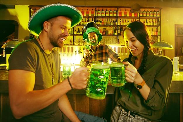 St. patrick's day party. glückliche freunde feiern und trinken grünes bier. junge männer und frauen tragen grüne hüte. pub interieur.