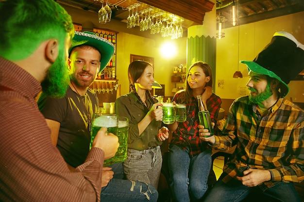 St. patrick's day party. glückliche freunde feiern und trinken grünes bier.