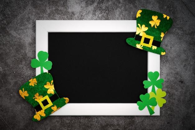 St. patricks day, festlicher koboldhut und grüne shamrocks auf fotorahmen