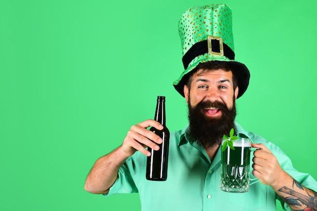 St patricks day glücklicher bärtiger mann hält becher mit bier irischer tradition bärtiger mann im koboldhut