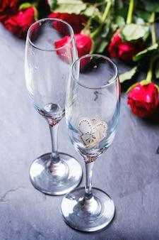 St. valentine-dekoration mit rosenblumenstrauß- und -champagnergläsern