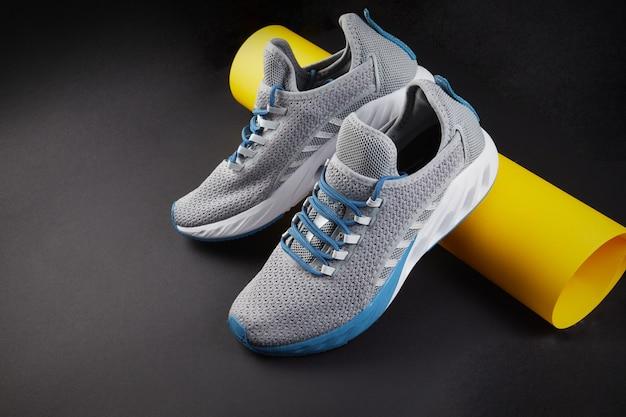 Stabilitäts- und polsterlaufschuhe. neuer laufschuh oder trainer ohne markenzeichen mit gelber papierröhre. sportschuhe für herren. paar sportschuhe.