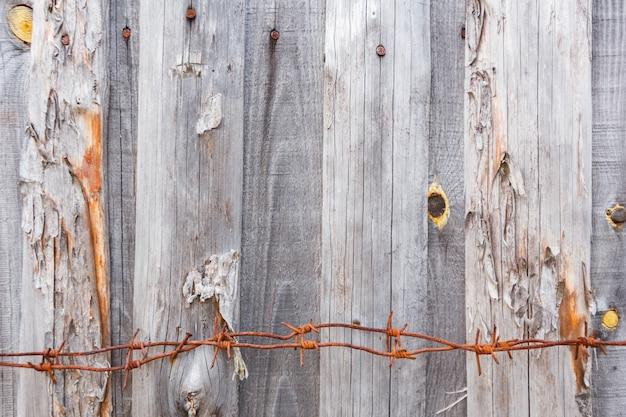 Stacheldraht an der unterseite eines zauns der grauen alten bretter