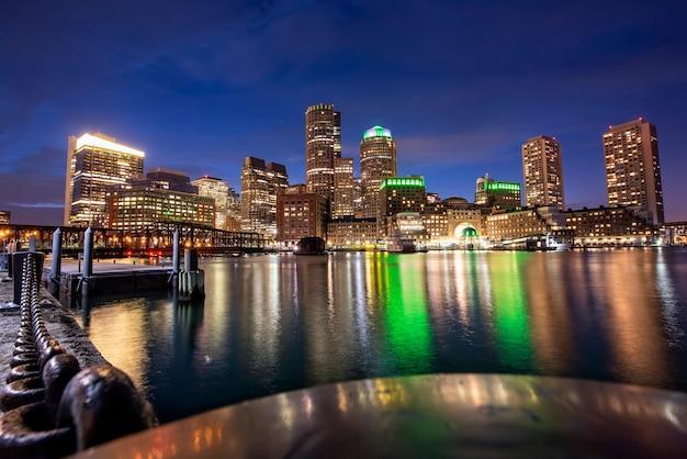 Stadt boston mit gebäuden und hafen bei nacht, wasserreflexionen und blauem himmel mit sternen