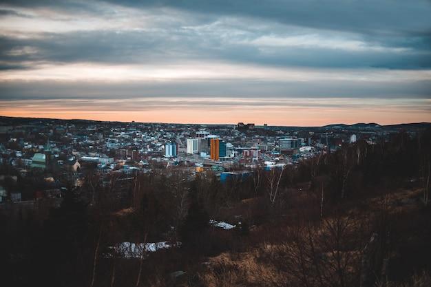 Stadt mit hochhäusern unter grauen wolken während des tages