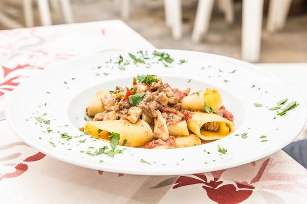 Stadt otranto, region apulien, süditalien. traditionelle paccheri-nudeln mit schwertfisch, serviert mit tomaten, petersilie, olivenöl. tageslicht, echtes restaurant in otranto.