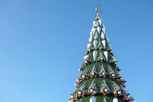 Stadt-weihnachtsbaum gegen einen blauen himmel. weihnachtsgirlanden. wochenenden und feiertage