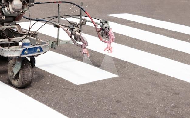 Stadtarbeiter malen zebrastreifen auf der straße mit malmaschine. nahansicht.