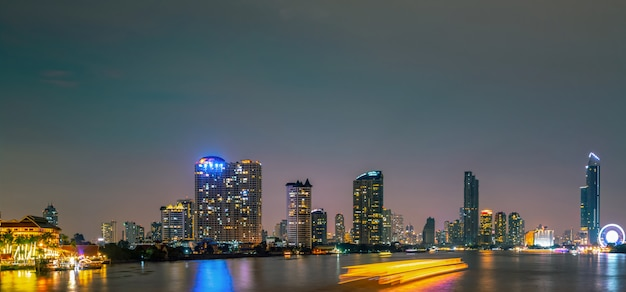 Stadtbild des modernen gebäudes nahe dem fluss in der nacht. modernes architekturbürogebäude. wolkenkratzer mit abendhimmel.