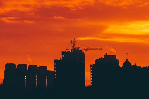 Stadtbild mit klarer brennender dämmerung. erstaunlicher warmer drastischer bewölkter himmel über dunklen schattenbildern von stadtgebäuden.