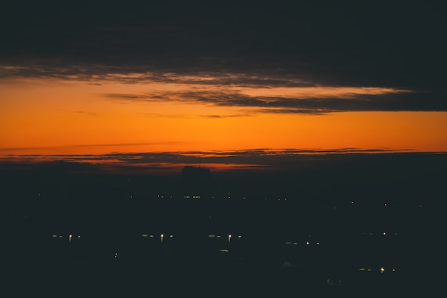 Stadtbild mit lebhafter feuriger morgendämmerung. erstaunlich warmer dramatischer bewölkter himmel über dunklen silhouetten von stadtbaudächern. orange sonnenlicht.