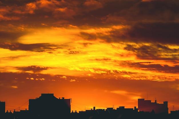 Stadtbild mit lebhafter feuriger morgendämmerung. erstaunlich warmer dramatischer bewölkter himmel über dunklen silhouetten von stadtgebäuden. orange sonnenlicht. atmosphärischer hintergrund des sonnenaufgangs bei bewölktem wetter. speicherplatz kopieren.