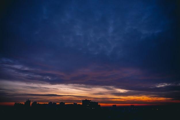 Stadtbild mit lebhafter warmer morgendämmerung. erstaunlicher dramatischer blauvioletter bewölkter himmel über dunklen silhouetten von stadtgebäuden. orange sonnenlicht.