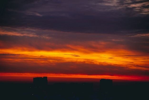 Stadtbild mit wunderbarer bunter feuriger morgendämmerung. erstaunlich dramatischer mehrfarbiger bewölkter himmel. dunkle silhouetten von stadtbaudächern.