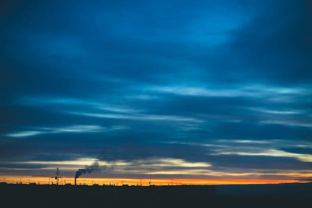 Stadtbild mit wunderschöner bunter, lebendiger morgendämmerung. erstaunlicher dramatischer blauer bewölkter himmel über dunklen silhouetten von stadtgebäuden. atmosphärischer hintergrund des orangefarbenen sonnenaufgangs bei bewölktem wetter. speicherplatz kopieren.