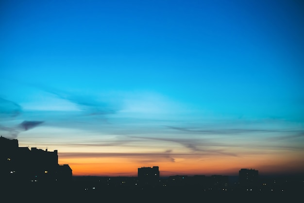 Stadtbild mit wunderschöner bunter, lebendiger morgendämmerung. erstaunlicher dramatischer blauer himmel mit lila und violetten wolken über dunklen silhouetten von stadtgebäuden. atmosphärischer hintergrund des orangefarbenen sonnenaufgangs. speicherplatz kopieren.
