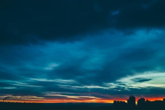 Stadtbild mit wundervoller vielfarbiger klarer dämmerung. erstaunlicher drastischer mehrfarbiger bewölkter himmel über dunklen schattenbildern von stadtgebäuden. atmosphärisch vom sonnenaufgang bei bewölktem wetter. copyspace.
