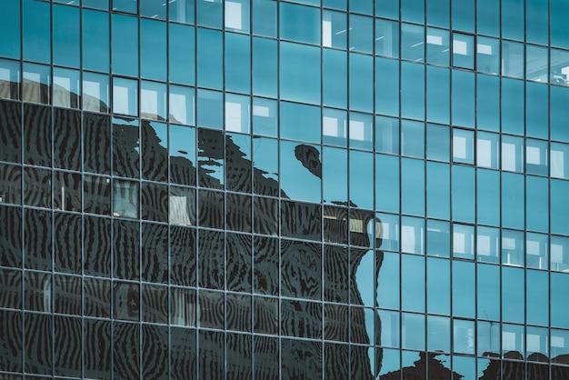Stadtbild-silhouetten spiegeln sich auf der verglasten fassade eines bürogebäudes wider