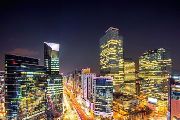 Stadtbild von südkorea. der nachtverkehr beschleunigt durch eine kreuzung im südkoreanischen stadtteil gangnam in seoul