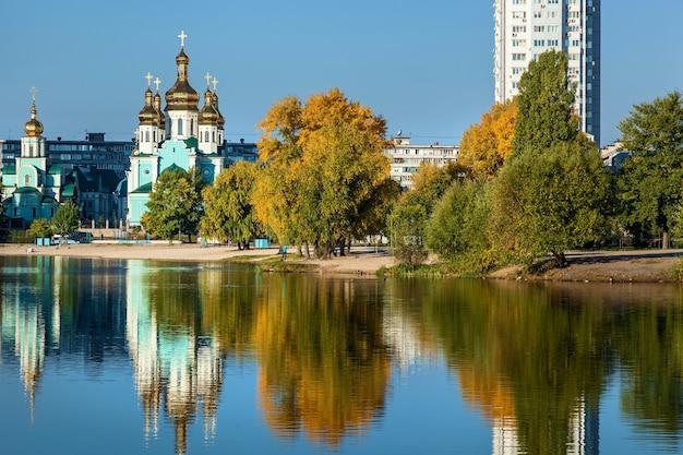 Stadtbildsee auf dem hintergrund von hochhäusern und kirche am herbstmorgen. ukraine, kiew, telbinsee.