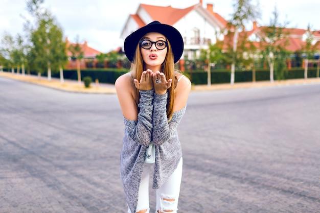 Stadtherbstmode-lebensstilporträt der jungen sinnlichen blonden frau, die trendige weiße jeans, hipster-brille und hut trägt, auf dem land posierend, spaß allein, weiche filmfarben tragend.