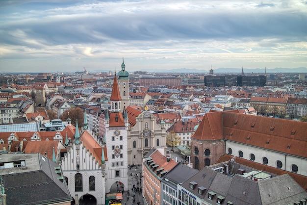 Stadtlandschaft, luftpanoramablick über dächern des historischen teils von münchen, deutschland des retro-hauses auf einem hintergrund des bewölkten sonnenuntergangshimmels.