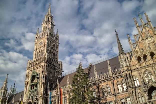 Stadtlandschaft mit blick auf das städtische gebäude des neuen rathauses auf einem hintergrund des blauen bewölkten himmels in der mitte von münchen, bayern, deutschland.