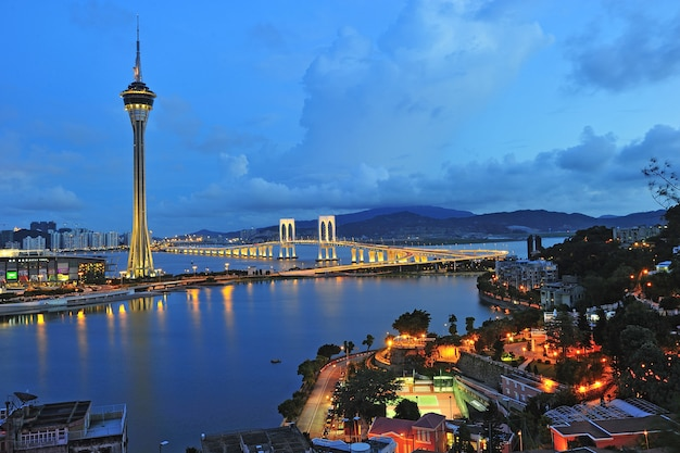 Stadtlandschaft von macao mit berühmtem reisendem turm unter blauem himmel nahe fluss in macao, asien.