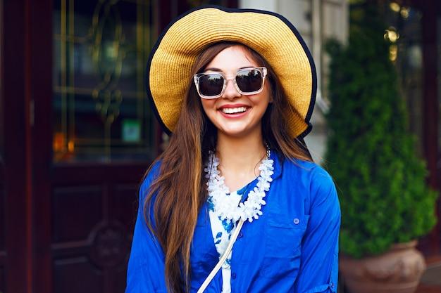 Stadtlebensstil-modeporträt des glücklichen hübschen mädchens, das allein geht, das spaß auf der straße, abendsonnenlicht, weinlesehut des retro-kleides, glückliche positive stimmung hat.