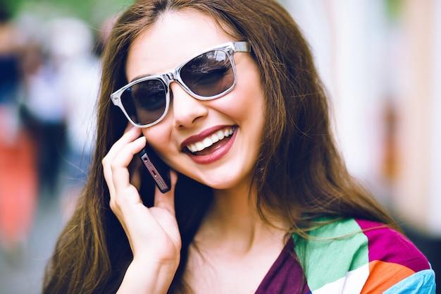 Stadtlebensstilporträt der hübschen brünetten frau unter verwendung des smartphones, des sprechens und lächelns, der hellen kleidung, der vintage filmfarben.