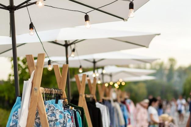 Stadtmesse. veranstaltungsdekor. weiße regenschirme, an denen glühbirnen hängen
