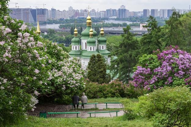 Stadtpark. die kuppeln der kirche und zwei sitzen auf einer bank. blühender flieder und wohngebäude im hintergrund.
