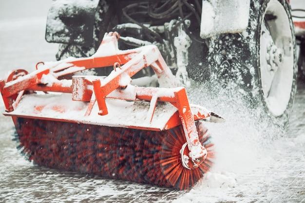 Stadtservice-reinigungsschnee, ein kleiner traktor mit einer drehenden bürste löscht eine straße im stadtpark vom frischen gefallenen schnee am wintertag, bürste - nahaufnahme.