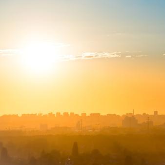 Stadtsonnenuntergang mit gebäudesilhouette auf orangefarbener skyline
